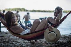 说谎在休息室的两个女孩在海滩在夏天 库存图片