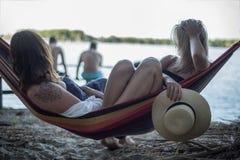 说谎在休息室的两个女孩在海滩在夏天 库存照片