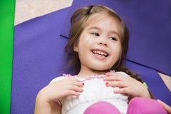 说谎在健身房的一张席子的一个微笑的小女孩的画象 免版税库存照片