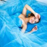 说谎在华美的蓝色礼服灰姑娘样式的美丽的新娘 图库摄影