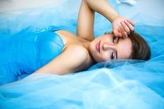 说谎在华美的蓝色礼服灰姑娘样式的美丽的新娘 免版税库存照片