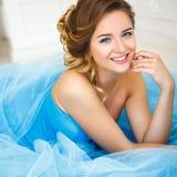 说谎在华美的蓝色礼服灰姑娘样式的美丽的新娘 库存图片