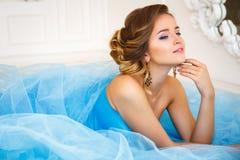 说谎在华美的蓝色礼服灰姑娘样式的美丽的新娘 免版税库存图片