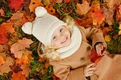 说谎在叶子的一件米黄外套的小俏丽的女孩在秋天 免版税库存照片