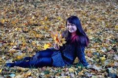 说谎在叶子的愉快的女孩 库存图片