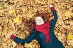 说谎在叶子的红头发人女孩在城市公园,秋季 库存图片