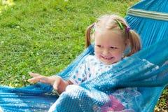 说谎在吊床和微笑的小女孩 免版税库存图片