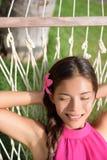 说谎在吊床的微笑的妇女在公园 库存图片