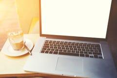 说谎在咖啡的便携式计算机在木桌上的附近在边路咖啡馆 库存图片
