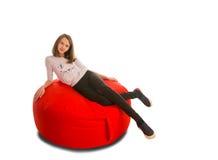 说谎在圆形红色装豆子小布袋椅子的女孩 库存图片