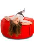 说谎在圆形红色装豆子小布袋椅子的年轻逗人喜爱的女孩 免版税库存图片