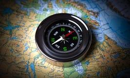 说谎在地图的旅游指南针 库存照片