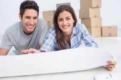 说谎在地板上和举行房子计划的夫妇的画象 免版税库存图片