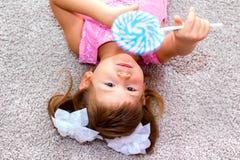 说谎在地板上和拿着棒棒糖的小女孩 库存照片