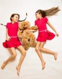 说谎在地板上和拿着玩具熊的两个微笑的女孩 库存照片