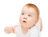 说谎在地板上和看边的好奇婴孩 免版税库存照片