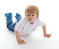 说谎在地板上的一个逗人喜爱的小男孩的画象 免版税库存图片