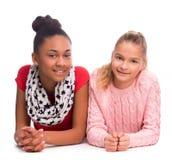 说谎在地板上的两个微笑的十几岁的女孩 库存照片