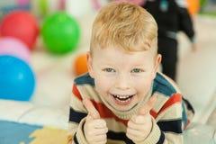 说谎在地板上的小男孩围拢由嘘五颜六色的气球 库存照片