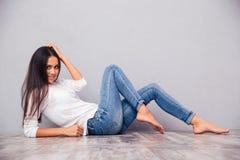 说谎在地板上的微笑的可爱的妇女 免版税图库摄影