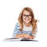 说谎在地板上的微笑的小学生女孩 免版税库存照片