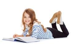 说谎在地板上的微笑的小学生女孩 免版税库存图片