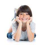 说谎在地板上的微笑的男孩 免版税库存图片