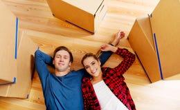 说谎在地板上的愉快的夫妇在有cordboard箱子的新的家 免版税库存照片