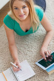 说谎在地板上的愉快的妇女做她的家庭作业使用片剂 库存图片