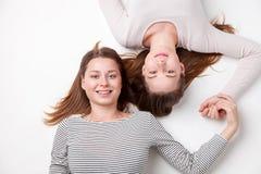 说谎在地板上的愉快的姐妹画象  库存图片