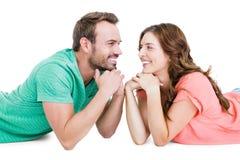 说谎在地板上的愉快的年轻夫妇互相看 免版税库存图片