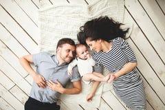 年轻说谎在地板上的父亲、母亲和逗人喜爱的婴孩 免版税图库摄影