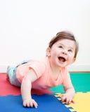 说谎在地板上的逗人喜爱的可爱的白种人微笑的男婴女孩画象在孩子屋子里 免版税库存图片