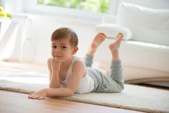 说谎在地板上的逗人喜爱的小男孩 免版税库存图片