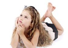 说谎在地板和作上的小女孩 免版税库存图片