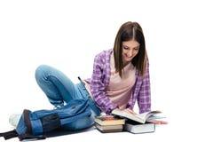 说谎在地板和阅读书上的女学生 免版税库存图片
