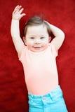 说谎在地板红色毯子的逗人喜爱的可爱的白种人微笑的男婴女孩画象在孩子屋子里 免版税库存照片
