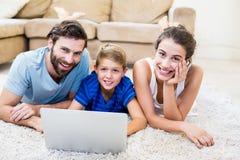 说谎在地毯和使用膝上型计算机的父母和儿子画象  库存照片