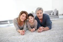 说谎在地毯地板上的愉快的家庭 库存图片
