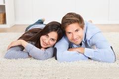 说谎在地毯的愉快的夫妇在客厅 免版税库存照片
