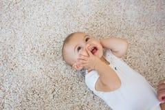 说谎在地毯的愉快的逗人喜爱的婴孩 免版税库存照片
