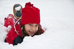 说谎在地面上的小女孩画象埋没由雪 免版税库存照片