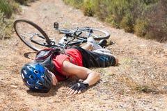 说谎在地面的受伤的骑自行车者在崩溃以后 免版税库存图片