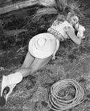 说谎在地面的微笑的女牛仔 图库摄影