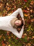 说谎在地面的微笑的年轻人在秋天公园 免版税库存照片