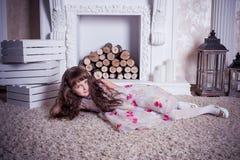 说谎在壁炉附近的可爱的女孩 免版税库存照片