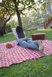 说谎在她的在一条方格的毯子的胃和读在公园的少妇,有野餐 免版税库存图片