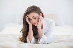 说谎在她的床上的白色睡衣的哀伤的偶然棕色毛发的妇女 免版税库存图片