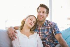 说谎在她的沙发的男朋友肩膀的女朋友  免版税库存图片