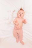 说谎在她的玩具兔宝宝附近的被编织的裤子的女婴 免版税库存图片